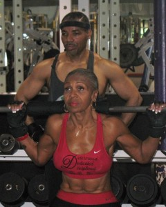 In training for her third bodybuilding competition, Ernestine Shepherd, 72, lifts weights under the watchful eye of her trainer, Raymond Day. Each week, Shepherd runs upward of 80 miles and hits the gym at least four times. The grandmother has become an inspiration to other senior women, who flock to her weekly aerobics classes at Union Memorial United Methodist Church in Baltimore. A UMNS photo by Barry Simmons. Photo #090400. Accompanies UMNS story #218. 5/20/09.