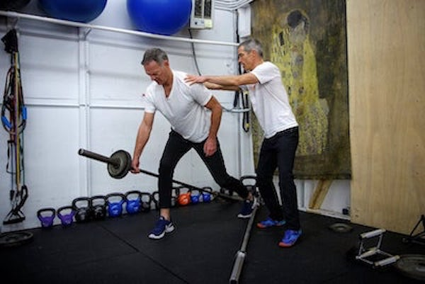 Functional training exercises like this Hip-hinged split-stance prybar row train solid body mechanics from whole-core engagement to proper head and foot positioning